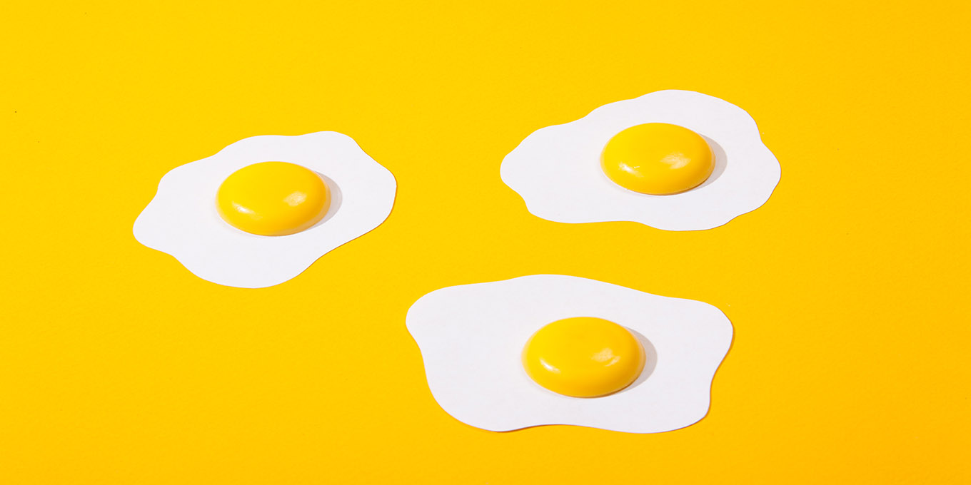 three-paper-scrambled-eggs-fried-eggs-located-on-a-yellow-paper-background